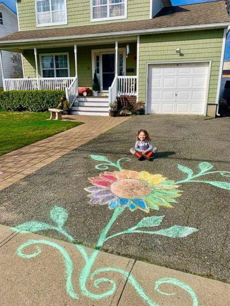 PHOTO: Violet, 4, sits in front of her Long Island home beside a rainbow flower created to spread hope amid the coronavirus crisis. (Allyson Uttendorfer)