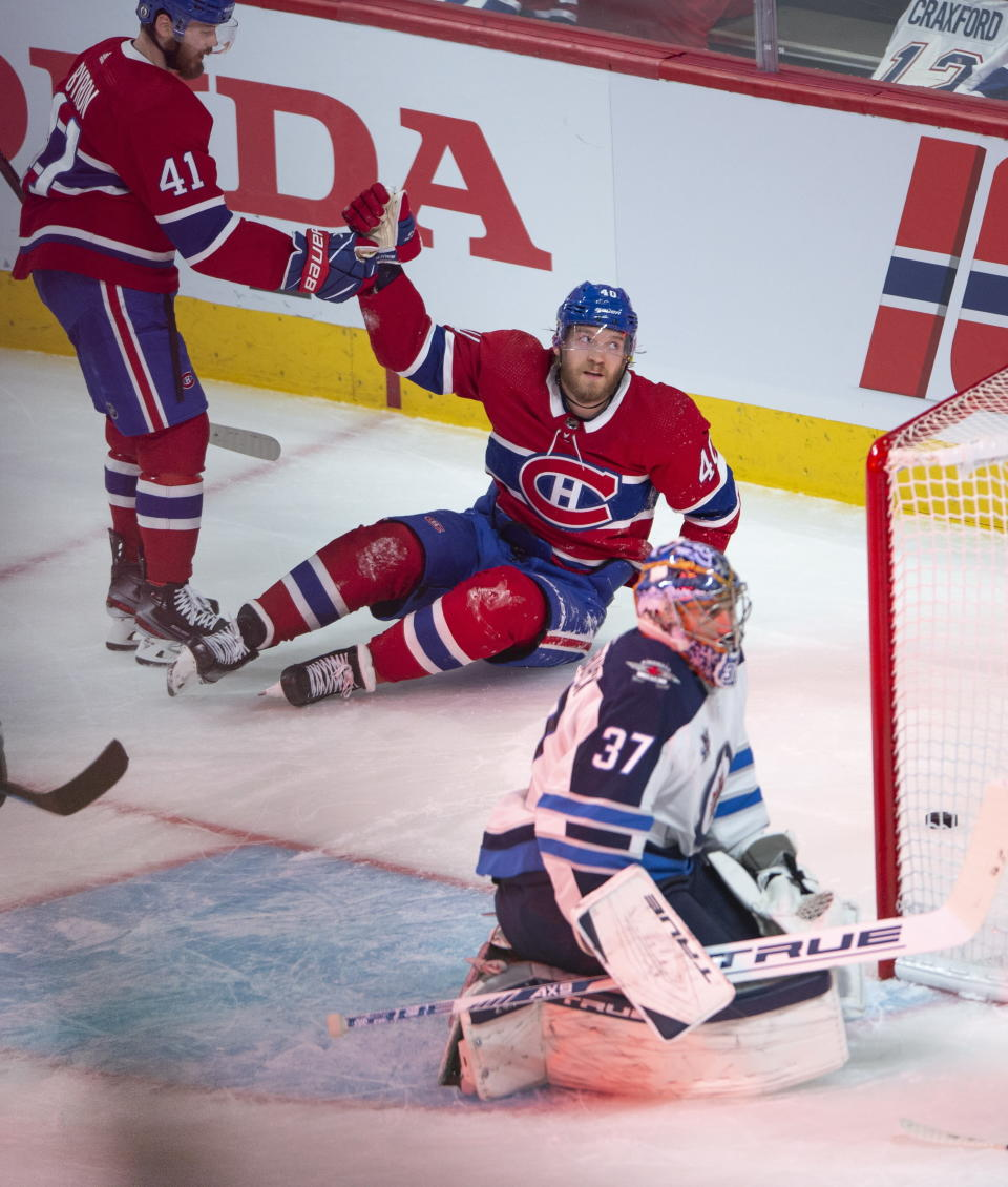 Montreal Canadiens' Joel Armia (40) celebrates with teammate Paul Byron (41) after scoring a shorthanded goal on Winnipeg Jets goaltender Connor Hellebuyck (37) during the second period of an NHL Stanley Cup playoff hockey game in Montreal, Sunday, June 6, 2021. (Ryan Remiorz/The Canadian Press via AP)