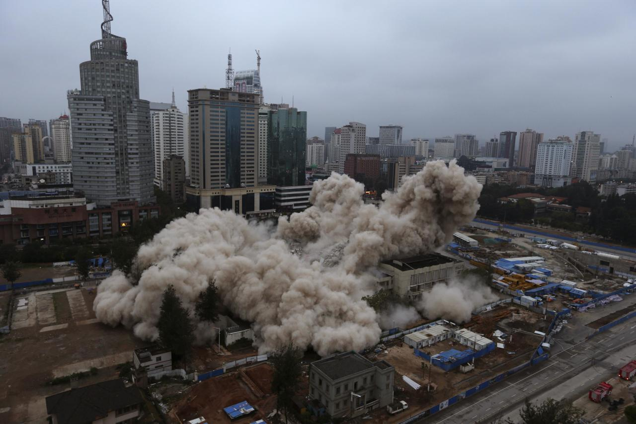 The Workers' Cultural Palace collapses after being demolished by explosives in Kunming, Yunnan province September 7, 2013. The 70-metre-high building has been a recreational centre for residents since being completed in 1982. REUTERS/Wong Campion (CHINA - Tags: SOCIETY TPX IMAGES OF THE DAY)