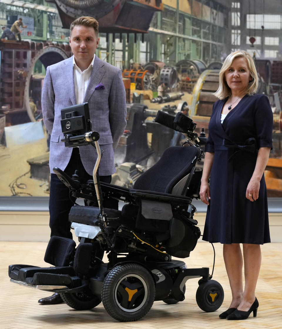 Lucy and Tim Hawking stand with the whelchair used by their late father Professor Stephen Hawking which has been acquired by the Science Museum Group, in London, Wednesday, May 26, 2021. Science Museum Group and Cambridge University Library will announce that they have acquired the historic contents of Professor Stephen Hawking's office (going to SMG) and his archive (going to CUL). (AP Photo/Kirsty Wigglesworth)