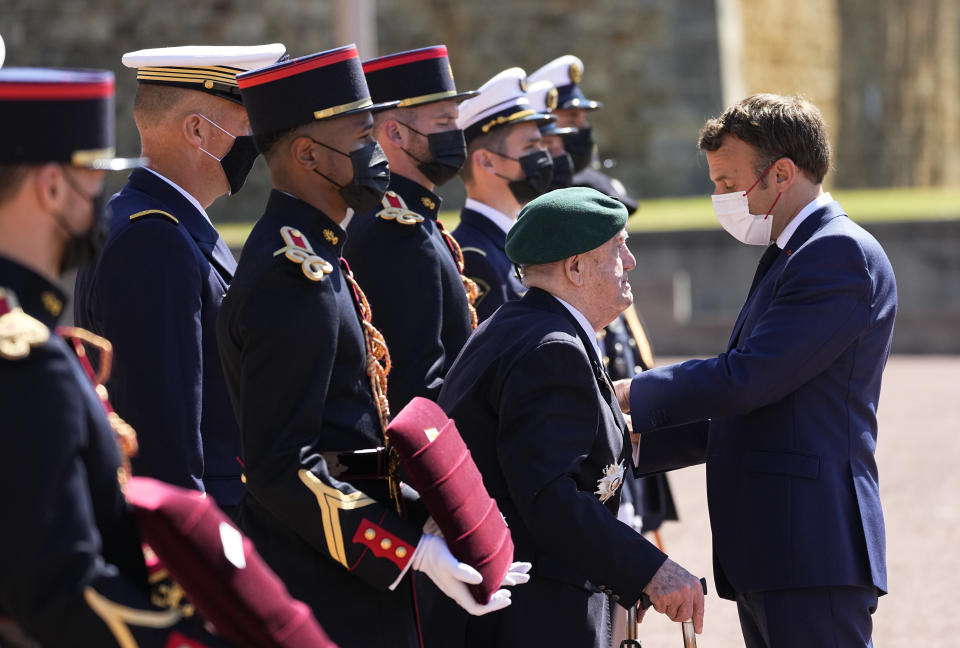 WWII French veterans Leon Gautier, 98 years old last survivor of the Kieffer Commando, left, is honored by French President Emmanuel Macron with the Legion of Honor during a WWII ceremony to mark the 81st anniversary of late French Gen. Charles de Gaulle's resistance call from London on June 18, 1940, at the Mont Valerien, in Suresnes, near Paris, Friday, June 18, 2021. The appeal, which was delivered on the BBC by Charles de Gaulle, served to rally his countrymen after the fall of France to Nazi Germany. (AP Photo/Michel Euler, Pool)