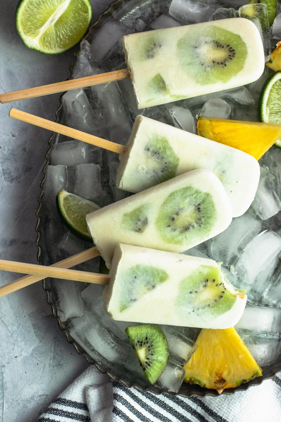 """<p>Pineapple and lime juice, coconut cream, bananas, and kiwis team up to bring you the most mouthwatering frozen treat of all: tropical paradise popsicles. Just one lick will transport you to a relaxing oasis far, far away.</p> <p><strong>Get the recipe</strong>: <a href=""""https://sugarandcloth.com/whole30-tropical-paradise-popsicles-recipe/"""" class=""""link rapid-noclick-resp"""" rel=""""nofollow noopener"""" target=""""_blank"""" data-ylk=""""slk:tropical paradise popsicles"""">tropical paradise popsicles</a></p>"""