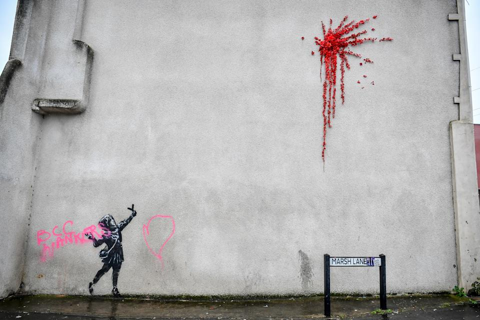 NOTE IMAGE CONTAINS SWEAR WORD A Banksy work of art on the side of a house on Marsh Lane, Barton Hill, Bristol, which has been vandalised with pink spray paint, the day after it was confirmed on Valentine's Day.