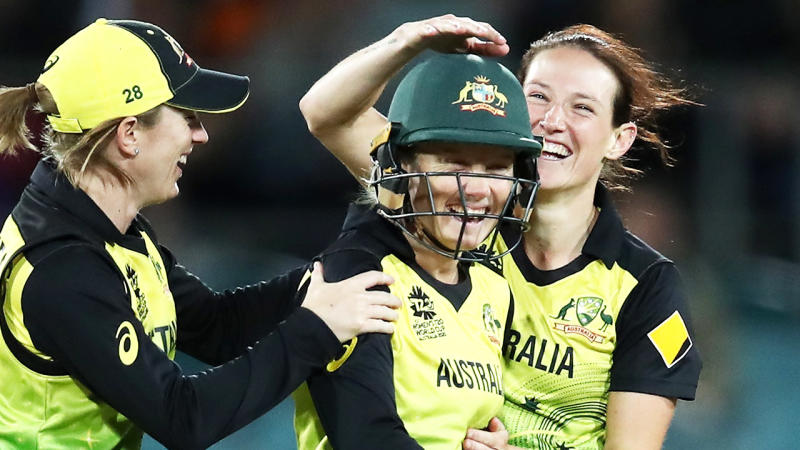 Alyssa Healy smiles celebrates with team mates.