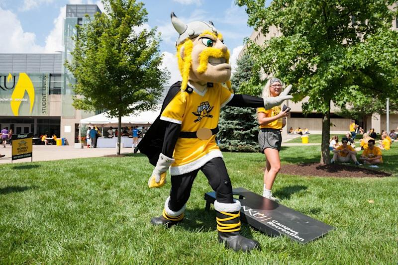 A college mascot who looks like a viking plays a bean bag toss game.