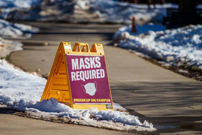 A sign alerting people that masks are required on campus