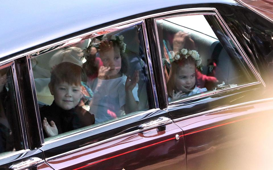 <p>The bridesmaids and page boys couldn't help but stare at the crowds as they drove past. (Getty) </p>