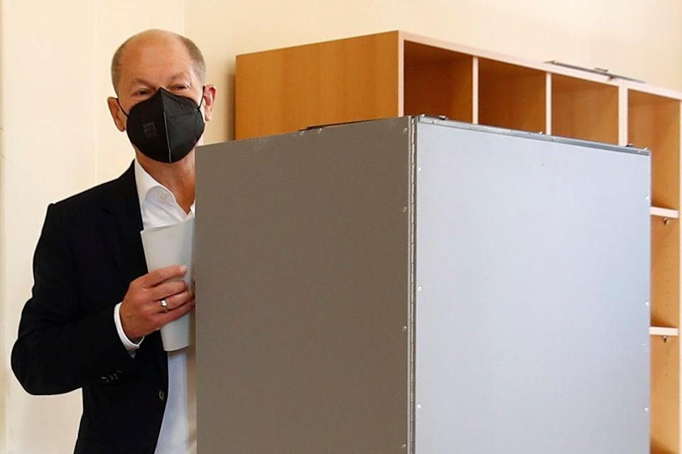 Olaf Scholz, Social Democratic Party candidate for chancellor, walks behind a polling booth to cast his vote (REUTERS)