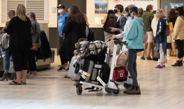 People wear masks as they wait in the arrivals area of the Ottawa International Airport. (Jean Delisle/CBC - image credit)