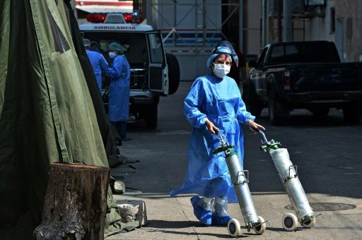 A health worker pushes oxygen tanks for patients infected with COVID-19 at a field hospital in Tegucigalpa, Honduras
