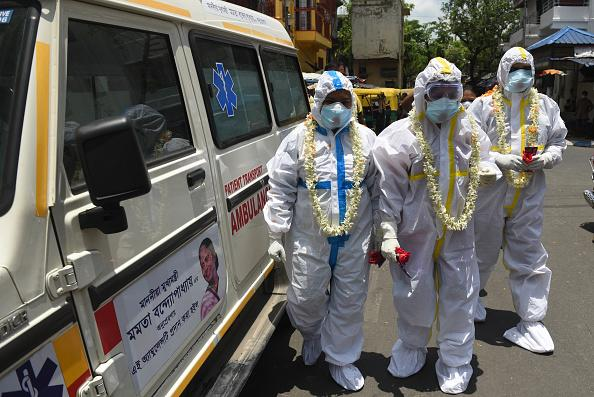 Kolkata Municipal Corporation (KMC) health department staff in PPE coveralls are greeted with garlands and a shower of flower petals before a swab collection exercise for COVID- 19 tests at Ward 68, Golpark in Kolkata, India.