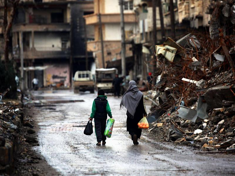 Syrians walk along a destroyed street in Raqqa. Officials estimate 150,000 people have returned to the city after the liberation – around half its pre-war population. But evidence of them is scant on the streets (Getty)