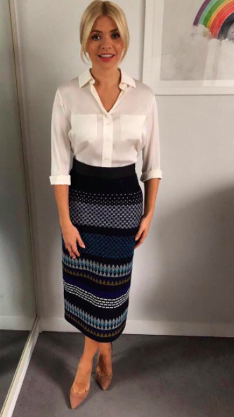 """<p>For this easy-to-imitate look, Holly shunned the high street and instead donned a jacquard-effect <a rel=""""nofollow noopener"""" href=""""http://www.next.co.uk/g772830s3?dclid=CJ2TwPjm_tYCFYnHUQodvfAM6Q#757147"""" target=""""_blank"""" data-ylk=""""slk:skirt"""" class=""""link rapid-noclick-resp"""">skirt</a> by Teatum Jones. She accessorised the look with suede heels from <a rel=""""nofollow noopener"""" href=""""https://www.office.co.uk/view/product/office_catalog/2,37/2419686386?P36=A1B2CZ&utm_source=AffiliateWindow&utm_medium=Affiliate&utm_campaign=http%3A%2F%2Fwww%2Estandard%2Eco%2Euk%2F&AFF=BU222025"""" target=""""_blank"""" data-ylk=""""slk:Office"""" class=""""link rapid-noclick-resp"""">Office</a> and a silk cream <a rel=""""nofollow noopener"""" href=""""https://www.winserlondon.com/silk-shirt-2524.html"""" target=""""_blank"""" data-ylk=""""slk:shirt"""" class=""""link rapid-noclick-resp"""">shirt</a> by Winser London. </p>"""