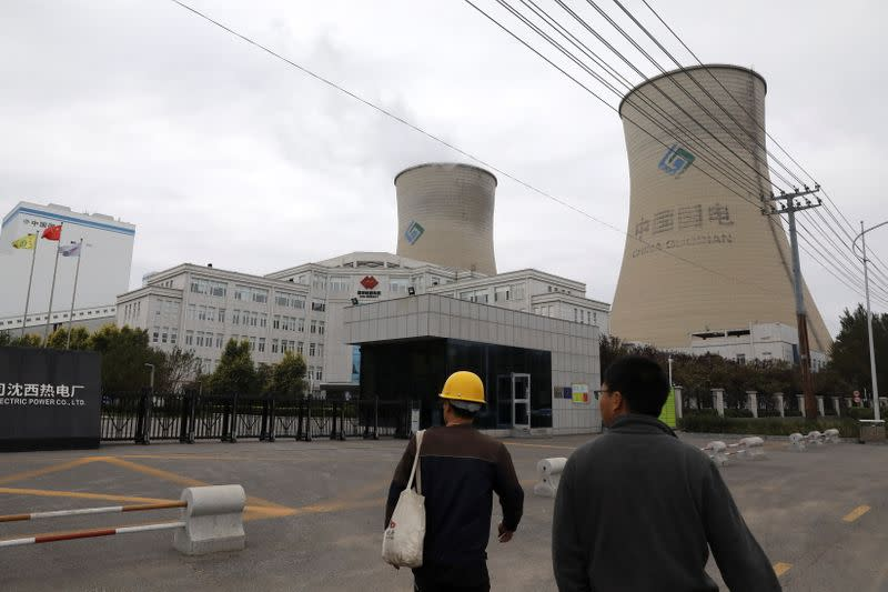 People walk past a coal-fired power plant in Shenyang