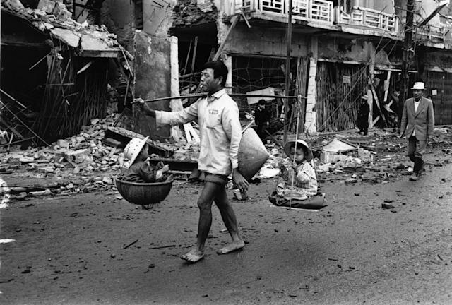 <p>A Vietnam War refugee returns to Hue, carrying two children in baskets suspended from his shoulder in March 1968. (Photo: Terry Fincher/Daily Express/Hulton Archive/Getty Images) </p>
