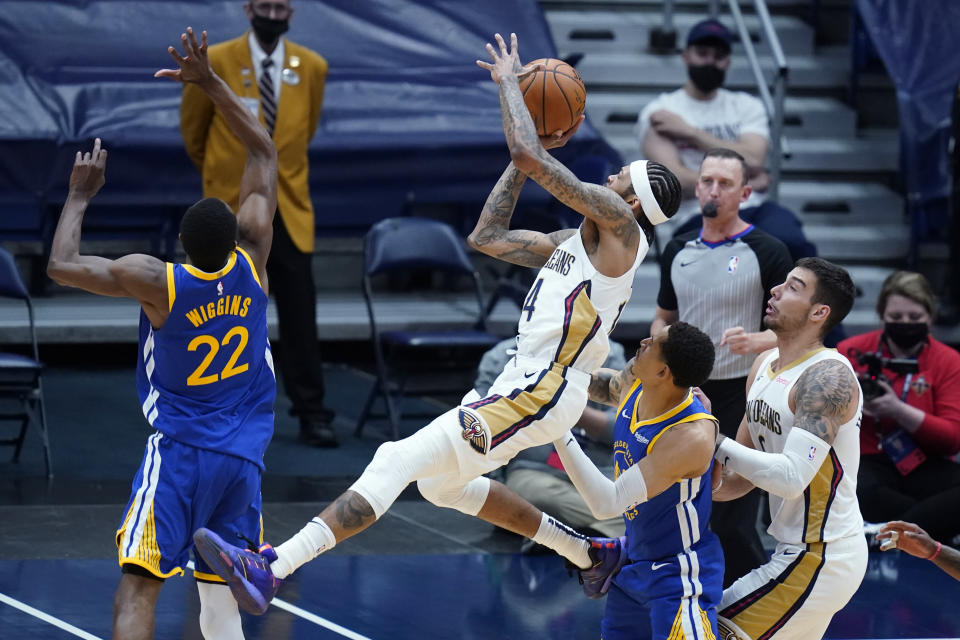 New Orleans Pelicans forward Brandon Ingram shoots between Golden State Warriors forward Andrew Wiggins (22) and guard Jordan Poole in the first half of an NBA basketball game in New Orleans, Monday, May 3, 2021. (AP Photo/Gerald Herbert)