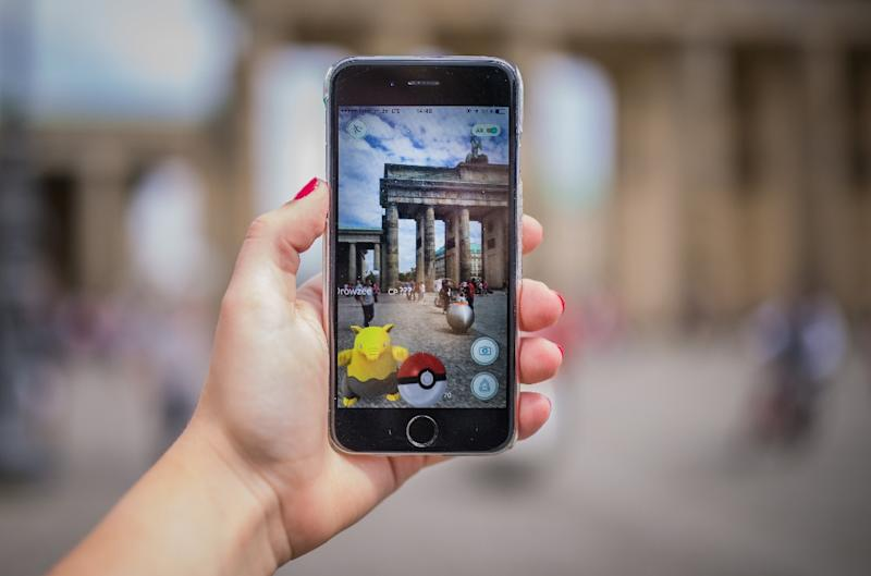 A woman points her smart phone at the Brandenburg Gate as she plays the Pokemon Go mobile game in Berlin (AFP Photo/Sophia Kembowski)