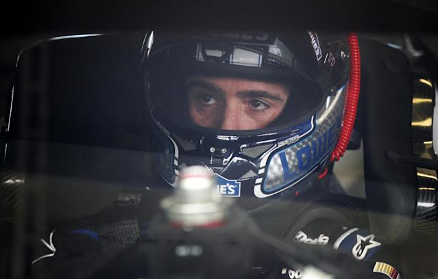 Driver Jimmie Johnson sits in his car waiting for the start of practice for Sunday's NASCAR Sprint Cup series auto race Friday, Nov. 15, 2013, at Homestead-Miami Speedway in Homestead, Fla.(AP Photo/Terry Renna)