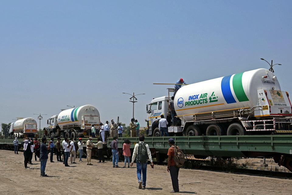 <p>Oxygen tankers being boarded on a special 'oxygen' train at a goods yard in Navi Mumbai </p> (AFP/Getty)
