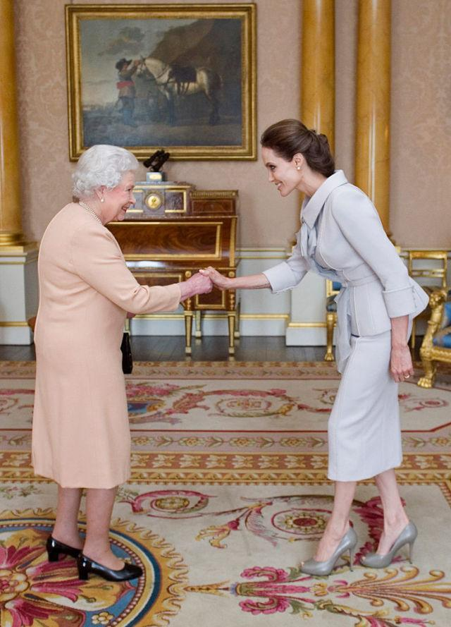 """<p>If you're a citizen of the United States, you can simply shake hands, but in Great Britain, <a rel=""""nofollow noopener"""" href=""""http://www.eonline.com/shows/the_royals/news/610777/8-things-you-should-never-do-when-meeting-the-royals"""" target=""""_blank"""" data-ylk=""""slk:men and women must bow or curtsy"""" class=""""link rapid-noclick-resp"""">men and women must bow or curtsy</a>. When Angelina Jolie, who is a US citizen met the Queen, she did a little of all three, because it's better to be safe than sorry.</p>"""