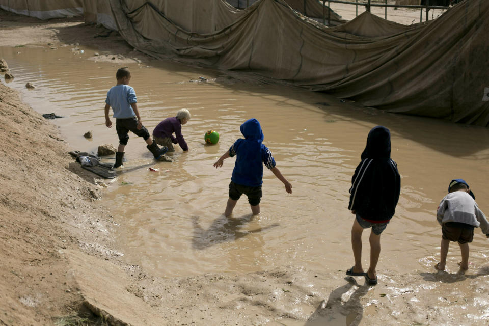 FILE - In this March 31, 2019 file photo, children play in a mud puddle in the section for foreign families at Al-Hol camp in Hasakeh province, Syria. At least eight children under the age of five have died in recent days from health problems linked to the dire conditions in a camp in northern Syria housing tens of thousands of female supporters of the Islamic State group and their children, the U.N. said Thursday, Aug. 13,2020. (AP Photo/Maya Alleruzzo, File)
