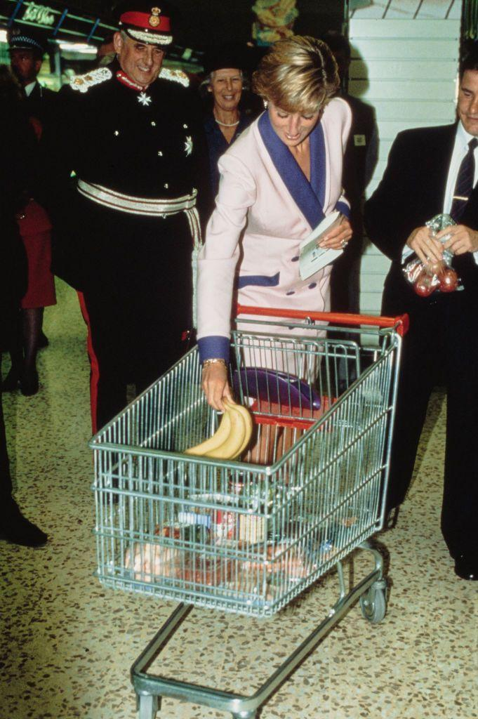 """<p>Princess Diana stocks up on bananas during a visit to a Tesco in Solihull. </p><p><strong>MORE</strong>: <a href=""""https://www.townandcountrymag.com/society/tradition/g27482477/royal-family-grocery-store-photos/"""" rel=""""nofollow noopener"""" target=""""_blank"""" data-ylk=""""slk:Photos of Queen Elizabeth, Princess Diana, and Other Royals at the Grocery Store"""" class=""""link rapid-noclick-resp"""">Photos of Queen Elizabeth, Princess Diana, and Other Royals at the Grocery Store</a><br></p>"""