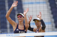 April Ross, right of the United States, and teammate Alix Klimeman wave after winning a women's beach volleyball match against Spain at the 2020 Summer Olympics, Tuesday, July 27, 2021, in Tokyo, Japan. (AP Photo/Petros Giannakouris)