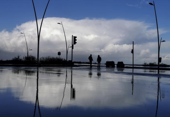 Residents walk along the seaside promenade in Beirut, Lebanon, Wednesday, Feb. 17, 2021. A strong storm in Lebanon brought cold temperatures and snow to Lebanon's mountains and heavy rainfall, strong winds on the Lebanese coast. (AP Photo/Hassan Ammar)