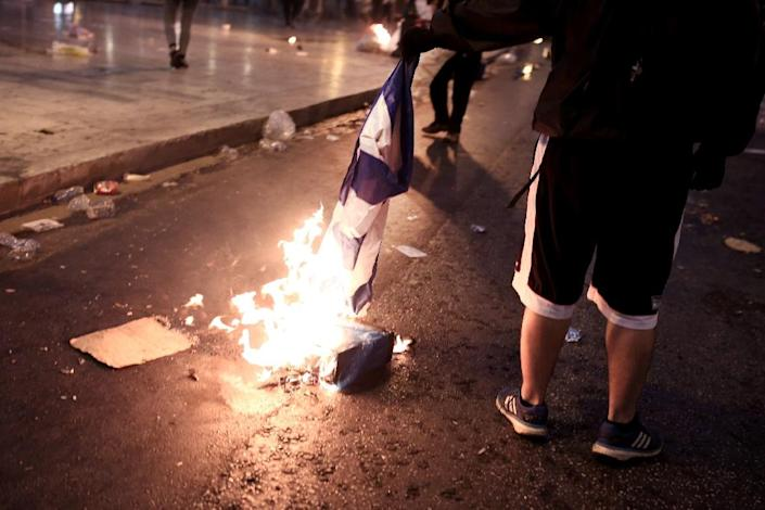 A protester burns a Greek flag in central Athens, during an anti-austerity protest on July 15, 2015 (AFP Photo/Angelos Tzortzinis)