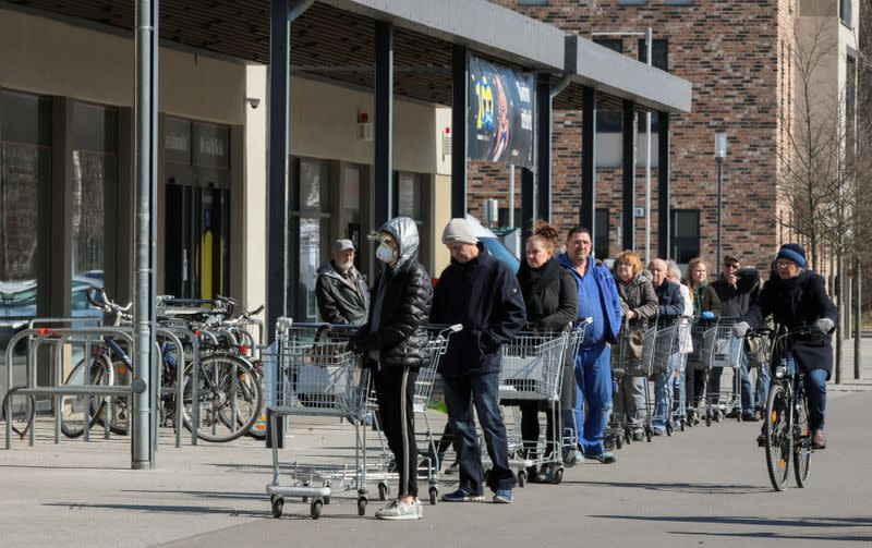 FILE PHOTO: People wait in a queue to enter a supermarket in Schulzendorf near Berlin, during the coronavirus disease (COVID-19) outbreak