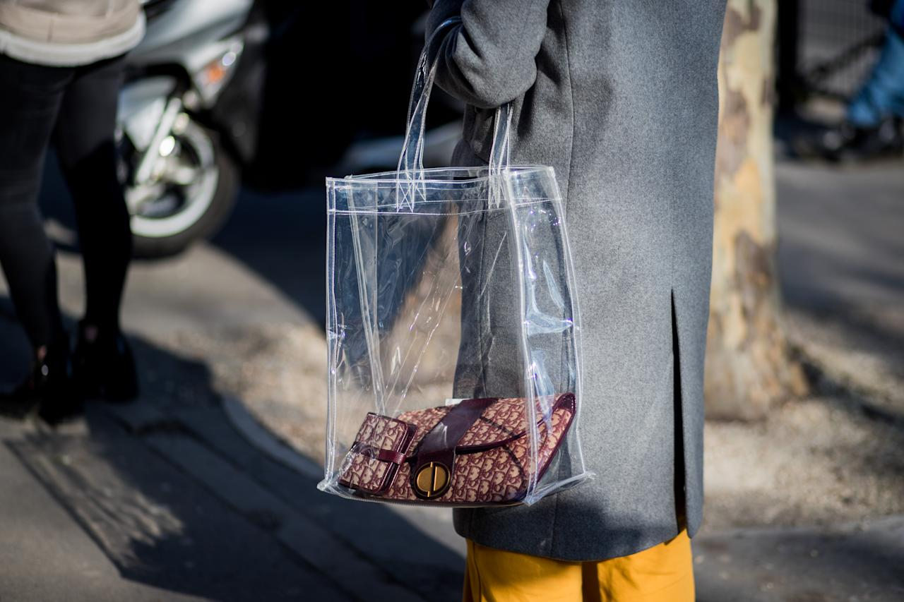 <p>Model carries her Dior bag and wallet in a clear plastic tote. (Photo: Getty Images) </p>