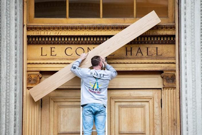 BERKELEY, CALIFORNIA - NOVEMBER 18: A member of a UC Berkeley work crews covers up the word LeConte Hall with planks of oak to match the massive wooden doors on the academic building that has been known for nearly 100 years as Old LeConte Hal Berkley, California. ( UC Berkeley photo by Irene Yi)