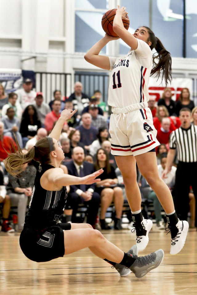 Robert Morris' Natalie Villaflor (11) shoots as St. Francis (Pa)'s Karson Swogger, left, defends during the first half of an NCAA college basketball game for the championship of the Northeast Conference women's tournament, Sunday, March 17, 2019, in Moon, Pa. (AP Photo/Keith Srakocic)