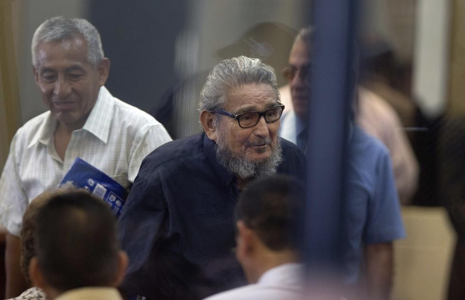 FILE - In this Feb. 28, 2017 file photo, Abimael Guzman, founder and leader of the Shining Path guerrilla movement, center, enters a courtroom at the Naval Base in Callao, Peru. The Peruvian government reported Saturday, Sept. 11, 2021, that Guzman died after an illness. (AP Photo/Martin Mejia, File)