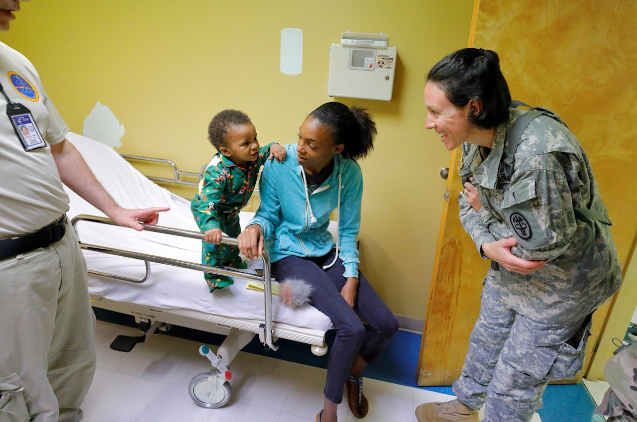 Lieutenant Commander Kate Hinkle of Silver Spring, an infectious diseases doctor at the Walter Reed Army Institute of Research who serves with the 602nd Area Support Medical Company when called upon, participates in the evaluation of a baby who was brought to the Schneider Regional Medical Center by his mother, in Charlotte Amalie, St. Thomas, U.S. Virgin Islands September 15, 2017.  REUTERS/Jonathan Drake