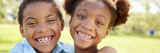 Two young African-American children smiling.