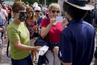 Tennis fans show their proof of vaccination cards for entry to attend the first round of the US Open tennis championships, Monday, Aug. 30, 2021, in New York. (AP Photo/Seth Wenig)