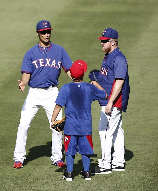 Texas Rangers' Yu Darvish, left, and Robbie Ross, right, visit with Haven Fielder, center, the son of Rangers' Prince Fielder, during practice before a baseball game against the Boston Red Sox, Saturday, May 10, 2014, in Arlington, Texas. (AP Photo/Jim Cowsert)
