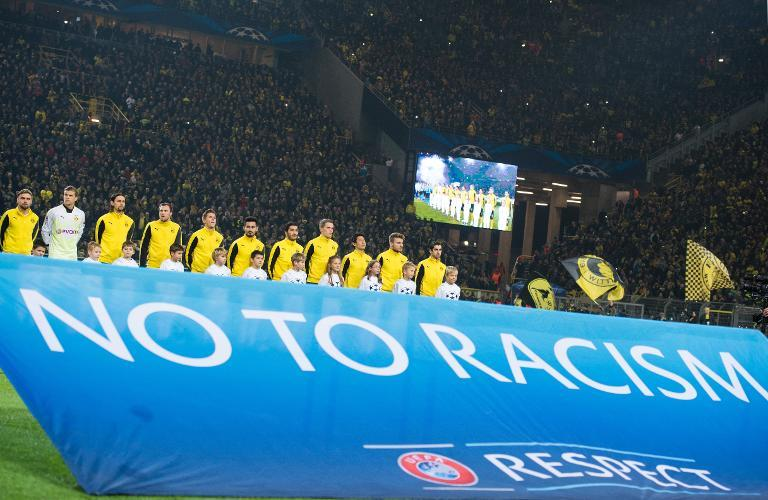 Borussia Dortmund's players stand behind a banner which reads 'No to Racism', ahead of a Champions League match in Dortmund, on December 9, 2014 (AFP Photo/Marius Becker)
