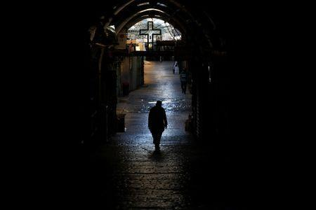 A priest walks down an ally in the Christian Quarter of Jerusalem's Old City June 21, 2016. REUTERS/Ronen Zvulun
