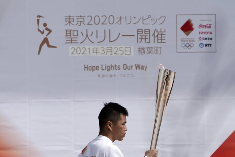 Local torchbearer Mahiro Abe, 19, carries the Olympic torch route of the first section of the Fukushima Torch Relay in Naraha, Fukushima prefecture, northeastern Japan, Thursday, March 25, 2021. The torch relay for the postponed Tokyo Olympics began its 121-day journey across Japan on Thursday and is headed toward the opening ceremony in Tokyo on July 23. (AP Photo/Eugene Hoshiko)