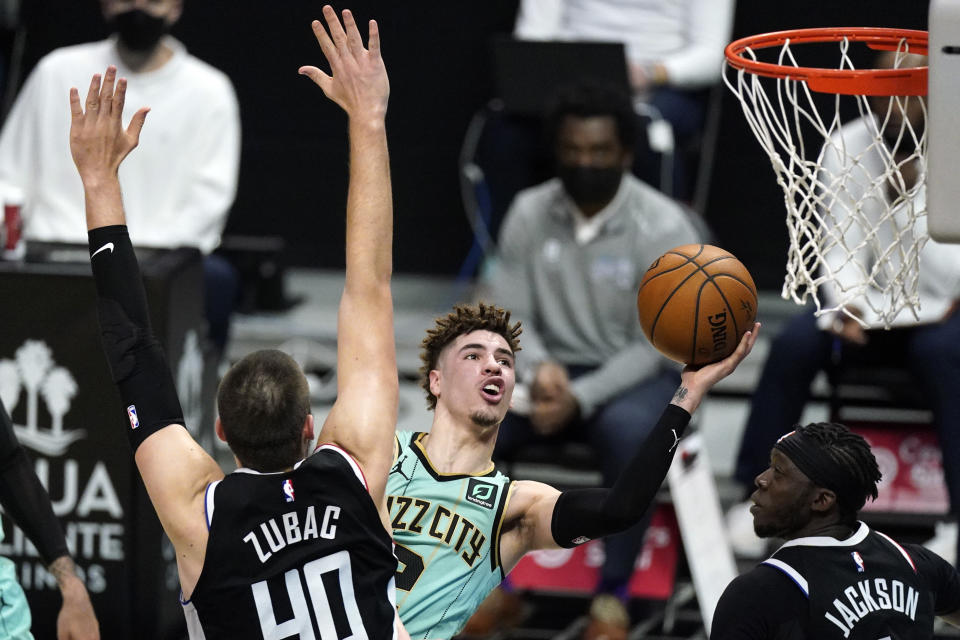 FILE - In this Saturday, March 20, 2021, file photo, Charlotte Hornets guard LaMelo Ball, center, shoots as Los Angeles Clippers center Ivica Zubac, left, and guard Reggie Jackson defend during the first half of an NBA basketball game in Los Angeles. Ball is expected to miss the rest of the season due to a broken right wrist, according to a person familiar with the situation. The person spoke to The Associated Press on Sunday on condition of anonymity because the team has not made the status of his injury public. He appeared to be hurt after a fall in the Hornets' 125-98 loss to the Clippers in Los Angeles on Saturday. (AP Photo/Mark J. Terrill, File)