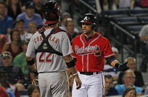 Atlanta Braves' Martin Prado, right, and Houston Astros catcher Carlos Corporan (22) exchange words in the seventh inning of a baseball game in Atlanta, Friday, Aug. 3, 2012. (AP Photo/John Bazemore)