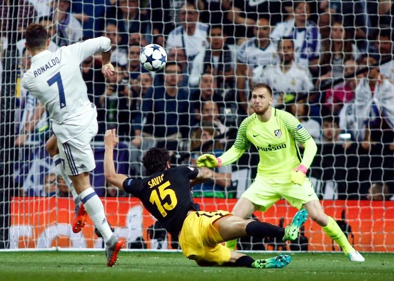 Real Madrid's forward Cristiano Ronaldo (L) shoots against Atletico Madrid's goalkeeper Jan Oblak (R) to score on May 2, 2017