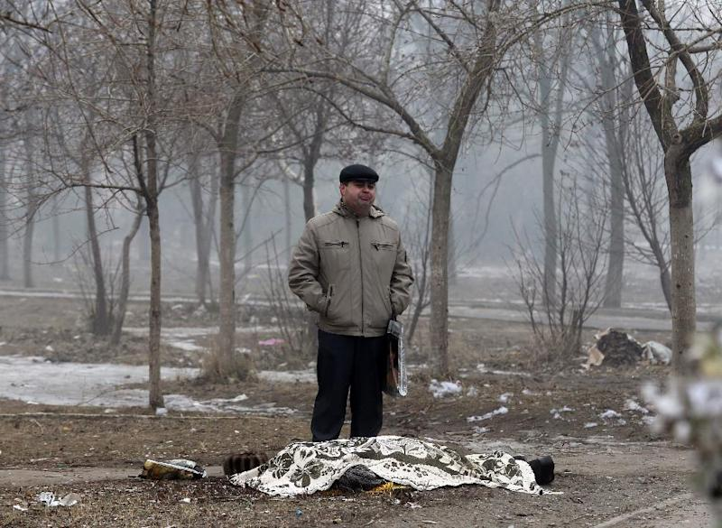 A man stands beside the covered body of a man who died after shelling in the southern Ukrainian port city of Mariupol on January 24, 2015 (AFP Photo/)