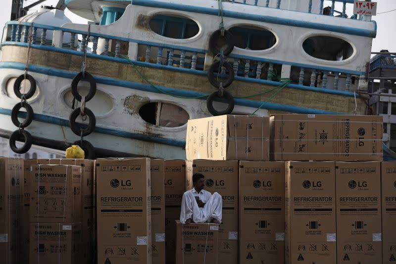 A worker waits to load goods onto a dhow bound for Iran along the creek in old Dubai