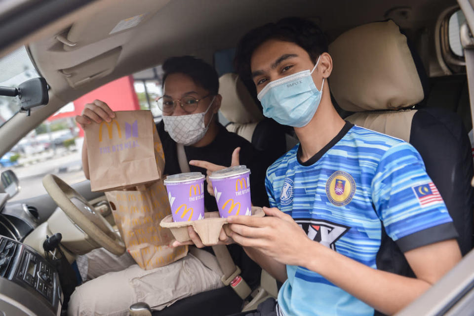 Customers pose with their BTS Meal at a McDonald's outlet in Seksyen 3, Shah Alam May 26, 2021. — Picture by Miera Zulyana