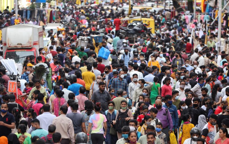 People walk in a crowded market amidst the spread of the coronavirus disease (COVID-19) in Mumbai