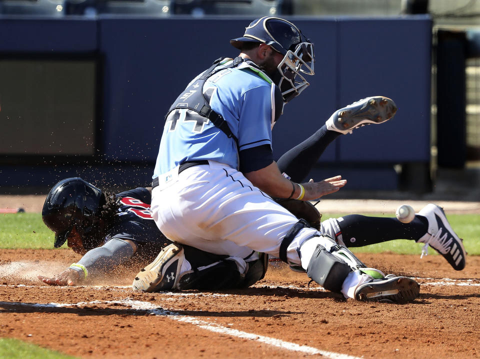 Atlanta Braves outfielder Justin Dean scores past Tampa Bay Rays catcher Kevan Smith on an RBI-single by Austin Riley to cut the Rays lead to 5-4 during the fourth inning of an MLB spring training baseball game at Charlotte Sports Park on Sunday, Feb. 28, 2021, in Port Charlotte, Fla. (Curtis Compton / Curtis/Atlanta Journal-Constitution via AP)