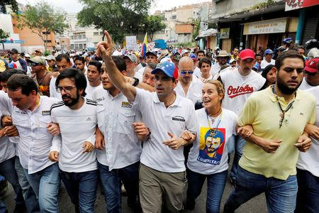 Lawmakers walk together with Venezuelan opposition leader and Governor of Miranda state Henrique Capriles (3rd R) and Lilian Tintori (2nd L) wife of jailed opposition leader Leopoldo Lopez, as they take part in a rally to honour victims of violence during a protest against Venezuela's President Nicolas Maduro's government in Caracas, Venezuela, April 22, 2017. REUTERS/Carlos Garcia Rawlins